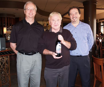 Bounty Cellars CEO Ron Pennington (left) presents a bottle of RIVER STREET RED to artist Kerry Waghorn, who created the original Capone caricature for the label. The presentation was at Le Bistro Chez Michel in North Vancouver. The proprietor, prominent restaurateur Philippe Segur (right) hosted the event.